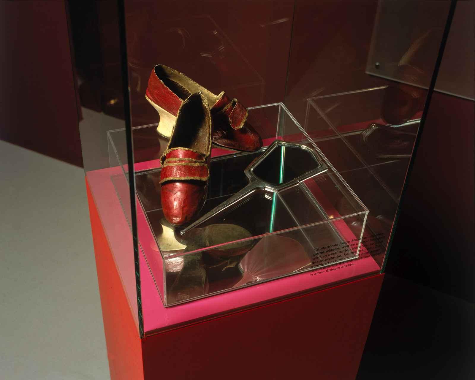 Vitrine mit mittelalterlichen Schuhen und Spiegel.