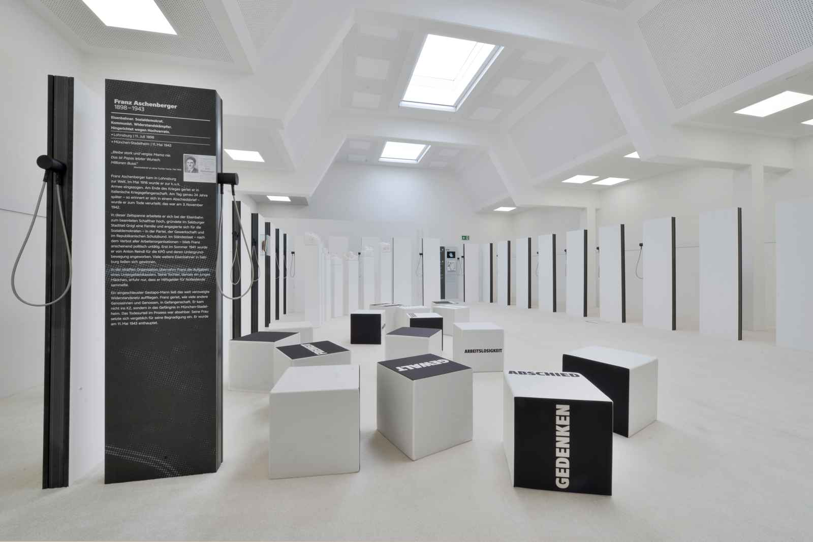 white cube - weißer Raum mit Biografiestelen und Sitzwürfeln