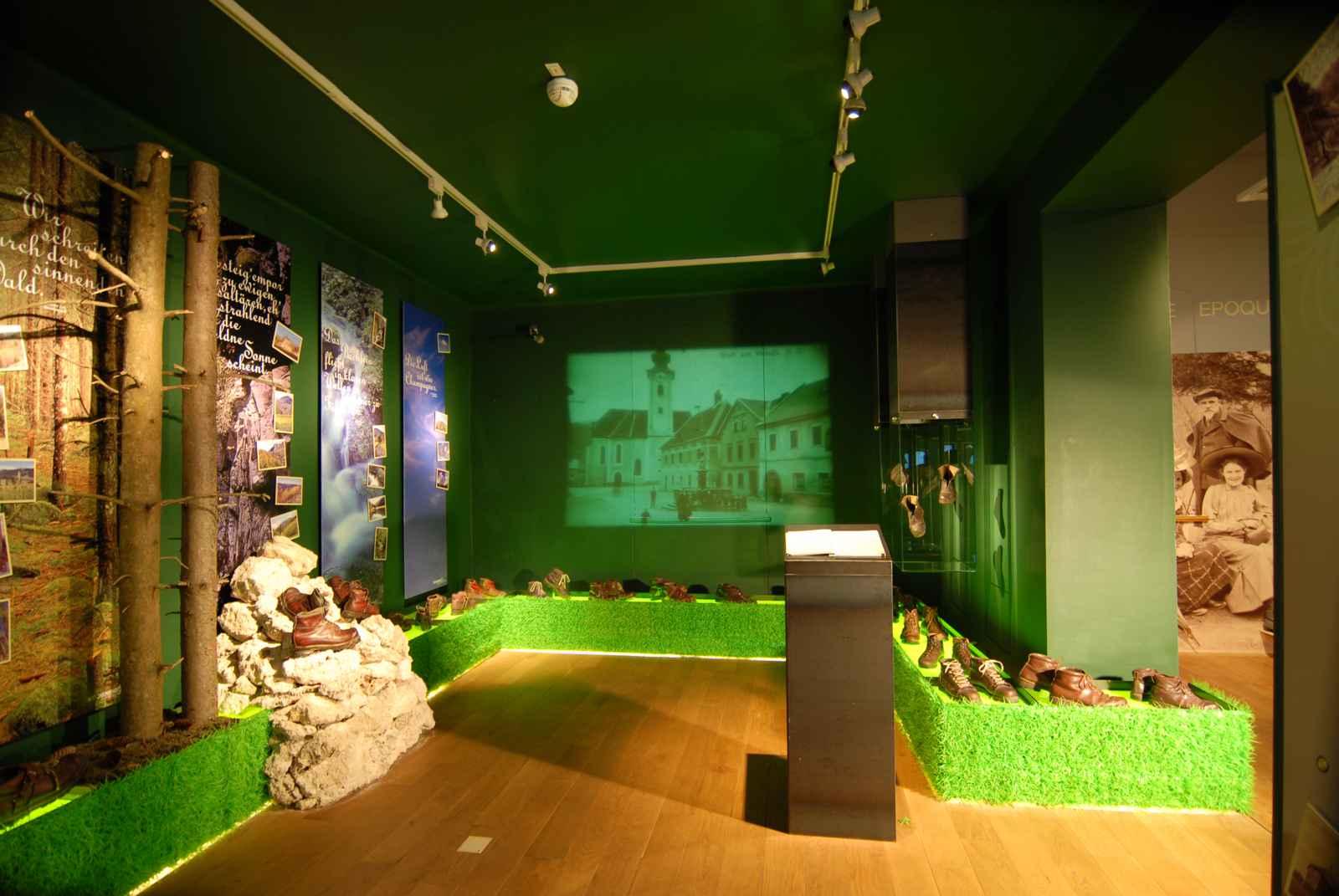 grüner Raum mit umlaufendem Grasband mit historischen Bergschuhen. Wald- und Felsinszenierung.