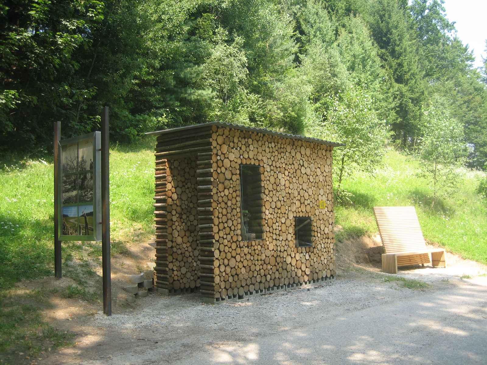 Holzarbeit, Informationstafel mit begehbarem Holzstoß und Sitzbank