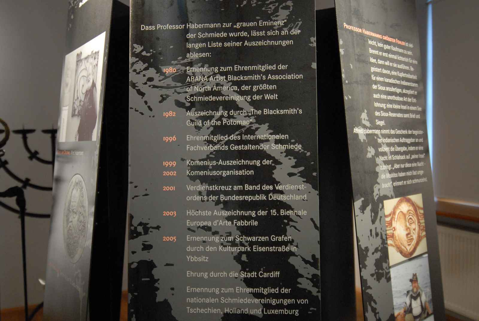 Biografiestelen kreisförmig angeordnet. Direktdruck auf Schwarzblech.
