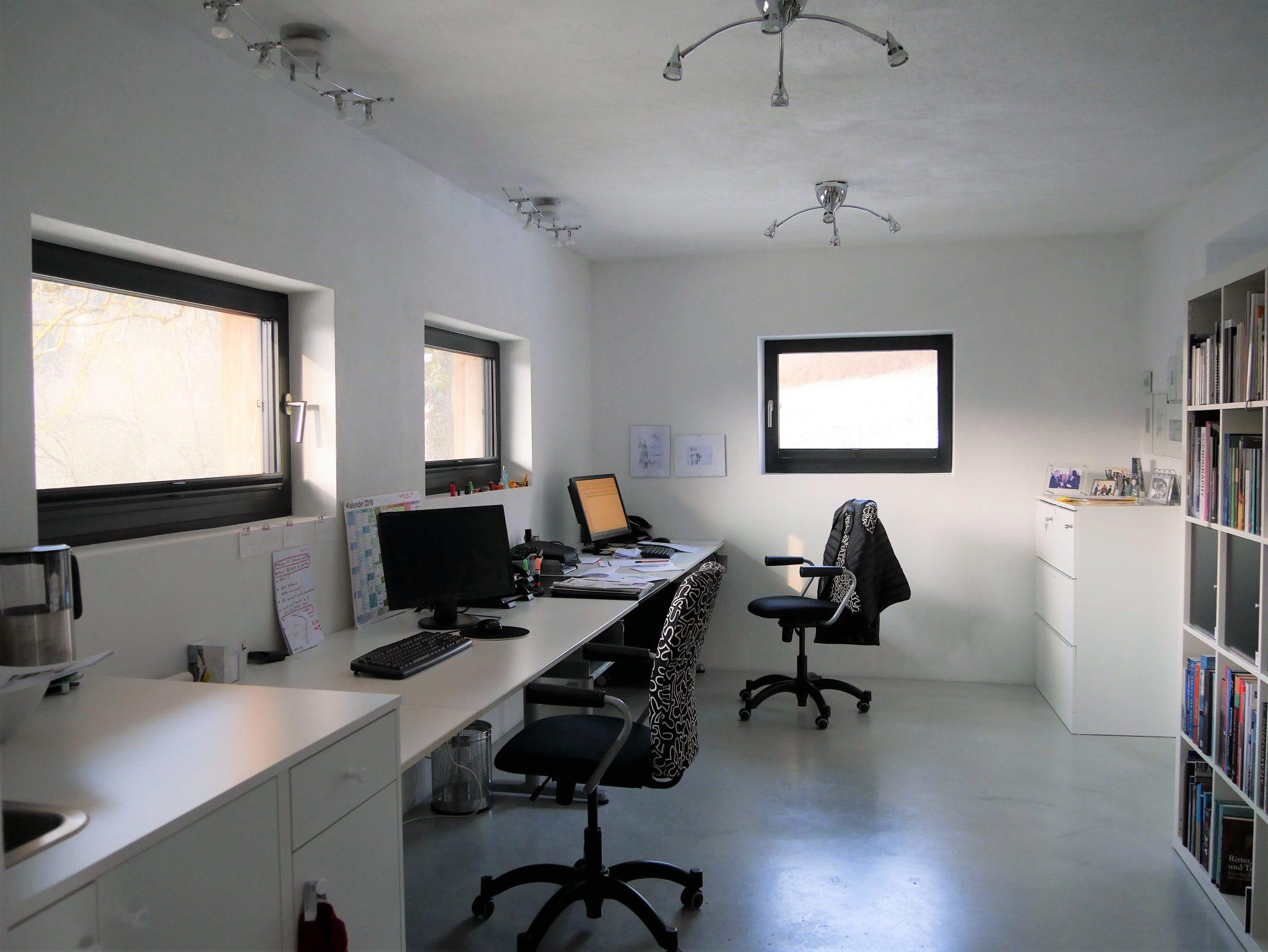 Büro St. Agatha mit Schreibtischzeile links vor hochliegenden Fenstern