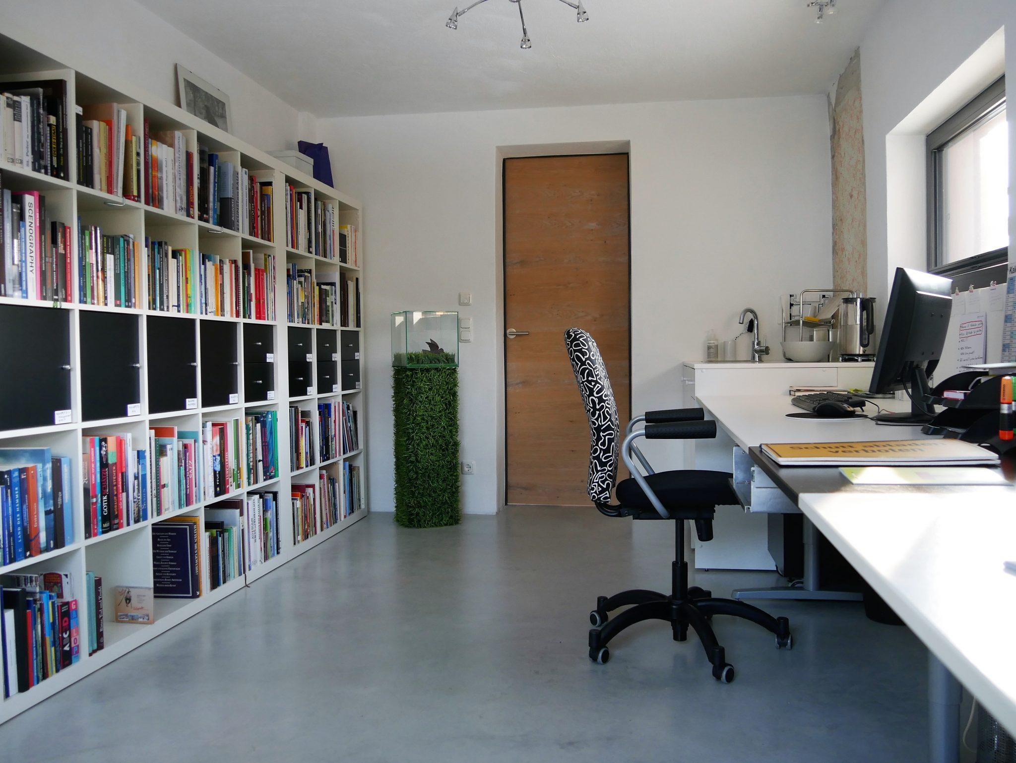 Büro mit Schreibtischzeile rechts und Bücherregal links
