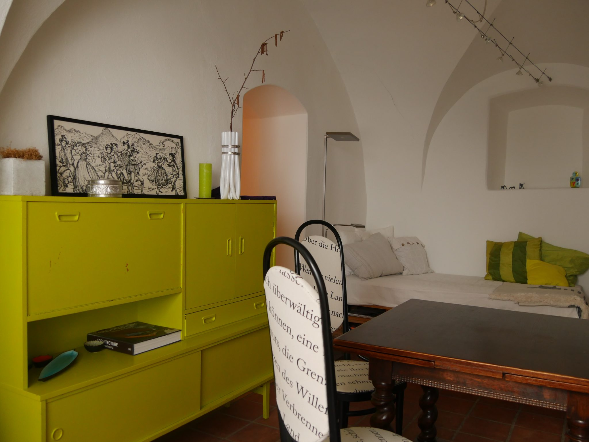 Bad Aussee Besprechungsbereich mit Tisch und zwei Stühlen im Vordergrund und Sitzecke im Hintergrund