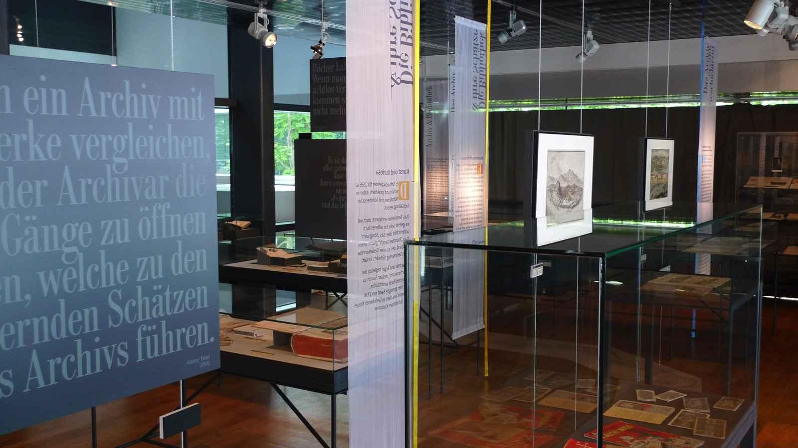 Raumeindruck mit Texttafeln, Vitrinen, Gemälden und Texthängern.