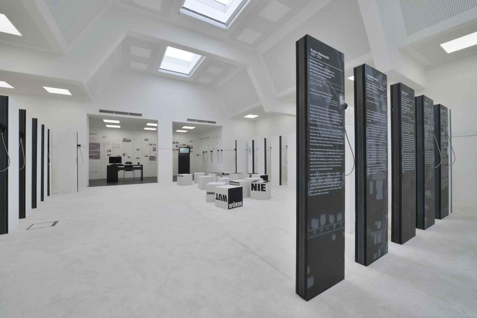 weißer Raum mit schwarzen Biografiestelen und Sitzwürfeln