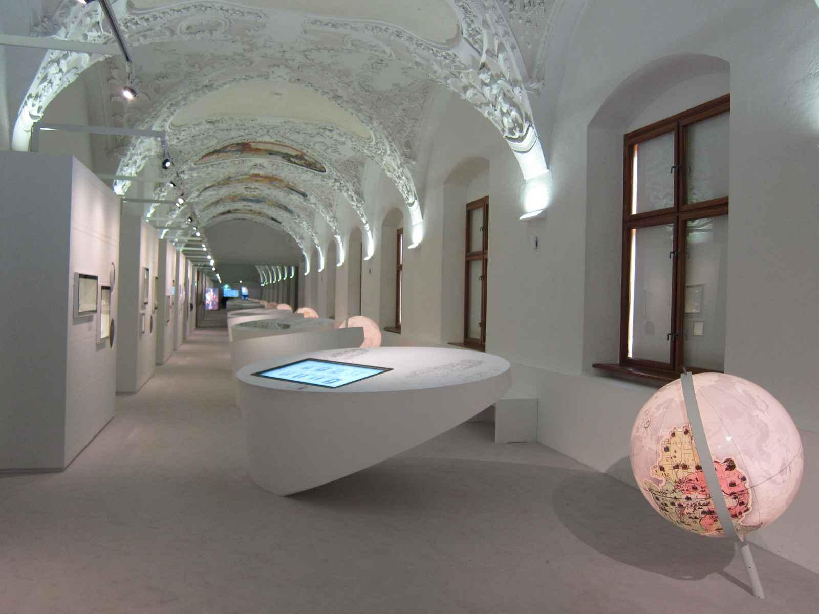 Raumeindruck Bibliothek mit Stuck Tonnengewölbe und ovalen Vitrinen. Im Vordergrund interaktiver Globus.