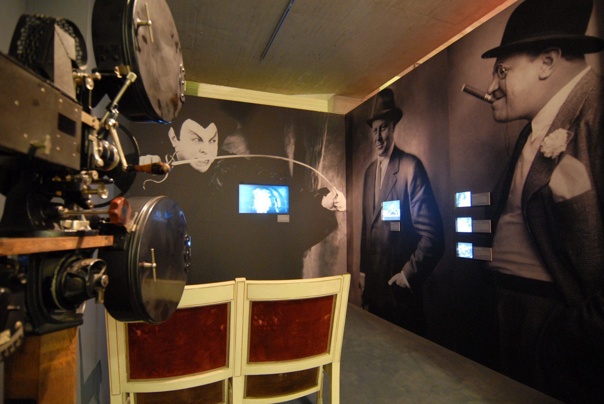 Stummfilm Filmapparat links, davor zwei historische Kinostühle, drei Großporträts von Emil Jannings mit Videos.