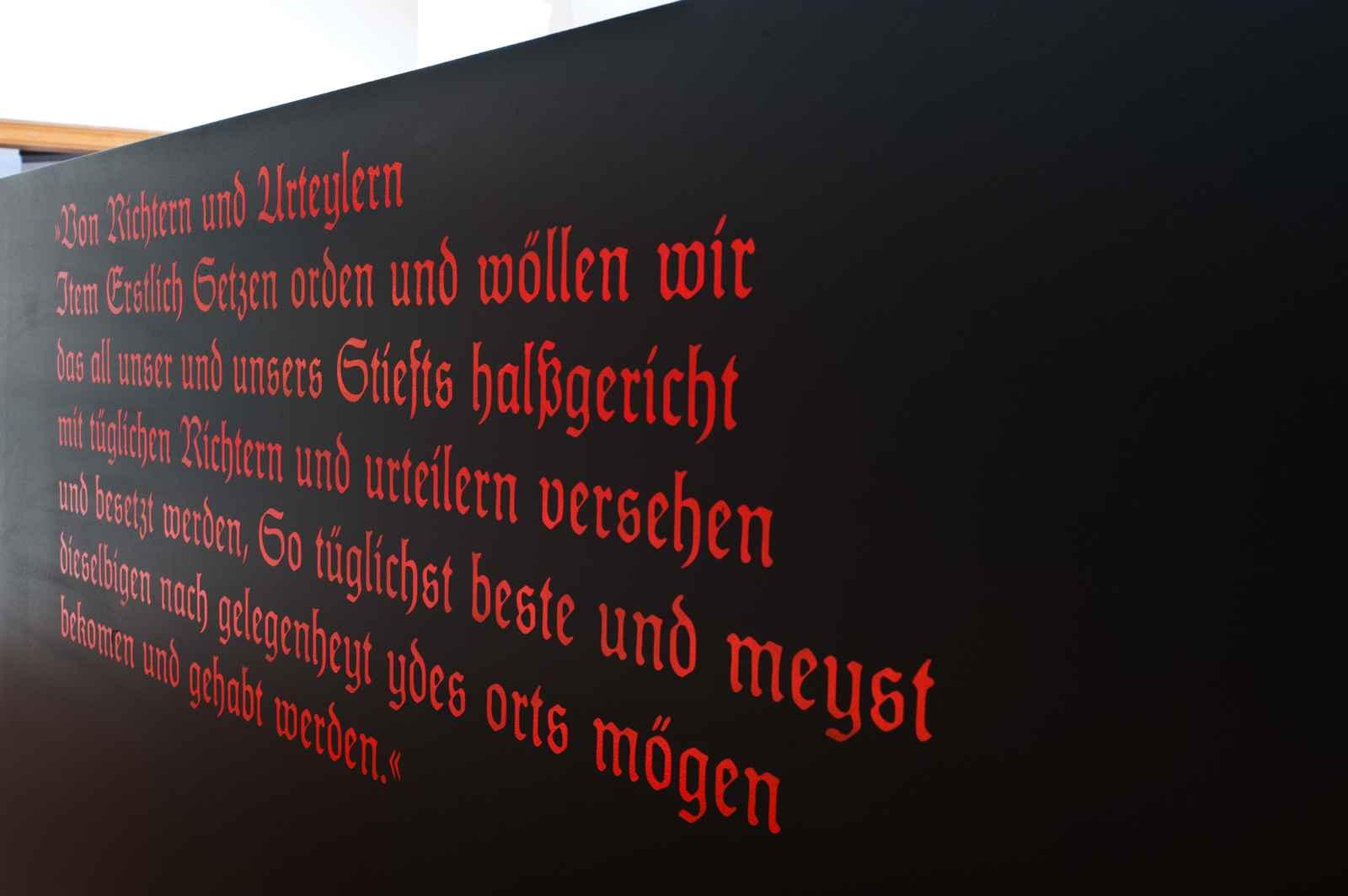 Zitat rote Frakturschrift auf schwarzem Grund